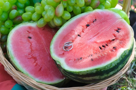 two and a half: Two wedding rings on half a watermelon. Beautiful juicy watermelon. Halves fresh watermelon, grapes, appel in a basket. Wedding day. Stock Photo