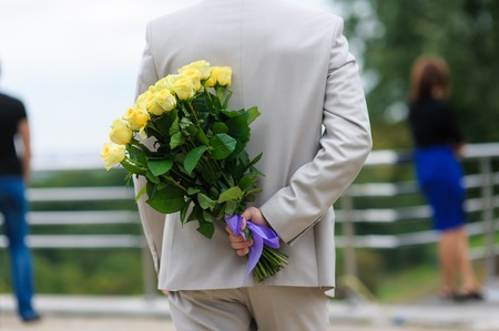 hides: Young man hides a bouquet of flowers behind his back. Yellow roses in a mans hand. The man in a suit. The figure of a girl in the background. Stock Photo
