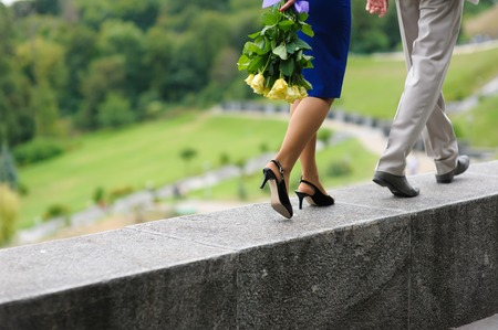 parapet wall: Young man and woman walking on a parapet wall. Yellow roses in hands at the girl. The woman is behind the man. Step by step. Hill, the park in the background.