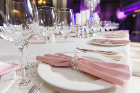 festively: Festively decorated table for a celebration. Pink napkin on a plate. Stock Photo