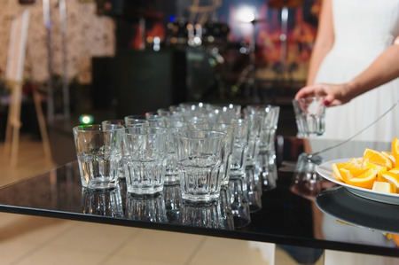 bartenders: Empty glasses on the table. Glasses for a cocktail reflected in the glossy surface of the table.  Bartenders hand holding a glass.