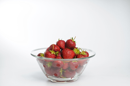 glass plate: Juicy, tasty strawberry on the glass plate. Strawberries in a glass plate on white background with copy space. Fresh strawberries lay on glass plate. Stock Photo
