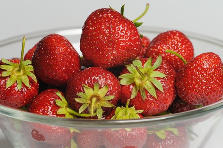 glass plate: Juicy, tasty strawberry on the glass plate. Strawberries in a glass plate on white background. Close-up fresh strawberries lay on glass plate.