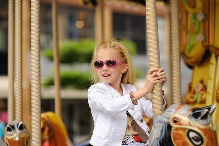 ruder: Kind Auf Alten Französisch Karussell in einem Ferienpark. Elegante Charming niedliche kleine Mädchen in der modernen Kleidung und Sonnenbrille genießt, sitzt auf Karussell-Pferd.