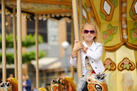 enjoys: Child On Old French carousel in a holiday park. Elegant Charming cute little girl in fashionable clothes and sunglasses enjoys, sitting on carousel horse.