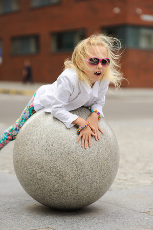 Elegant Charming cute little girl in fashionable clothes and sunglasses having fun outdoors. Large stone ball. Stock Photo