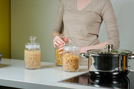 unboiled: Woman cooking. Three Closed Glass jars Jar With Raw Pasta. Woman is going to cook pasta.