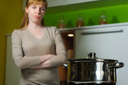 electric stove: Pan on electric stove in the kitchen. Young woman annoyed, frustrated. Redhead woman cooking soup in home kitchen. Housewife looking in to pan. Stock Photo
