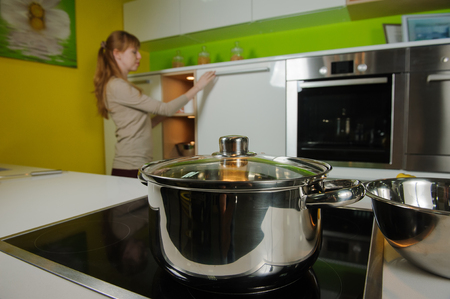 electric stove: Pan on electric stove in the kitchen. Redhead woman cooking soup in home kitchen.
