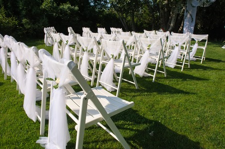 White Decorated Chairs On A Green Lawn Set In Rows For The Wedding Ceremony