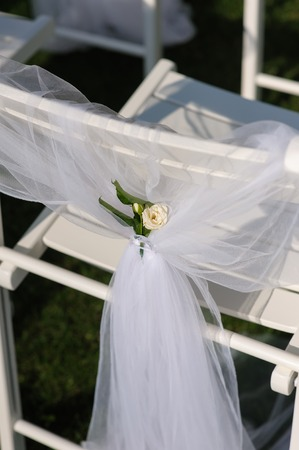 lawn chair: White chair with a small flower. White decorated chairs on a green lawn. Chairs set in rows for the wedding ceremony. They are decorated for the festive event. Chairs are on the green lawn outside. Stock Photo