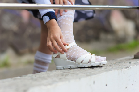 little girl putting on her sandals outdoors