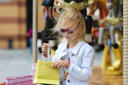 enjoys: Child On Old French carousel in a holiday park. Elegant Charming cute little girl in fashionable clothes and sunglasses enjoys, sitting with full shopping bags. Reviewing purchases on city street.