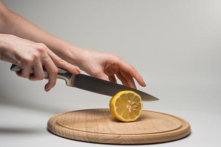 Girl cuts frash lemon into slices on a cutting board. Stock Photo