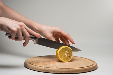 frash: Girl cuts frash lemon into slices on a cutting board. Stock Photo