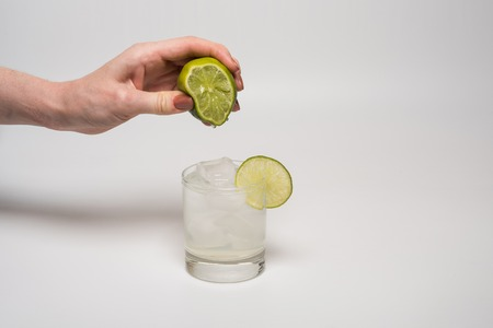 squeezing: Female hand squeezing lime into glass cocktail Stock Photo