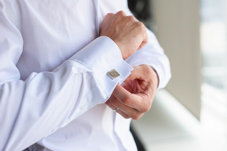suit  cuff: Male buttons cufflinks. Businessman buttons cufflinks in white shirt. Groom in morning wears shirt to a wedding. Stock Photo