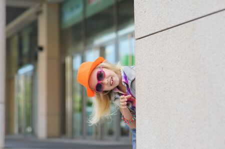 Adorable happy child in sunglasses and orange hat. Shop windows in the background. Girl peeking around the corner. Blond hair fluttering in the wind. Stock Photo