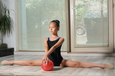 ball stretching: Stretching Little japanese Girl. Attractive, beautiful Asian girl doing gymnastics exercises in hall rhythmic gymnastics. Window, jalousie in background. Child sitting on splits. Red ball in hand.
