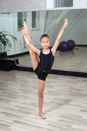 splits: Girl gymnast doing splits in gymnasium. Mirror in background. Cute little Asian girl gymnast with a highly raised leg. Vertical splits. Stretching Little japanese Girl. Stock Photo