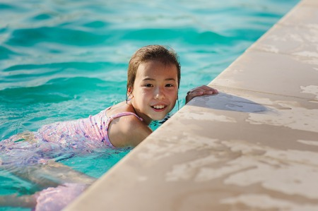 looking into camera: Asian child girl in swimming pool. Girl smiling, looking into camera