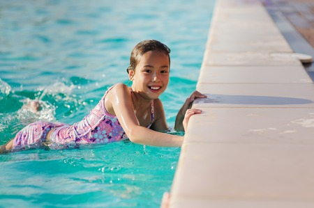looking into camera: Asian child girl in swimming pool. Girl smiling, looking into camera. Kids learning to swim.