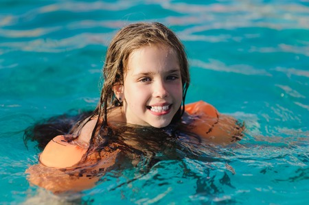 Caucasian child girl in swimming pool. Girl smiling, looking into camera. Child with water wings in swimming pool. Kids learning to swim. Stock Photo
