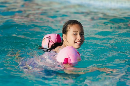 water wings: Asian child girl in swimming pool. Girl smiling, looking into camera. Child with water wings in swimming pool. Kids learning to swim.