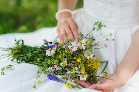 The bride holds in hand a bouquet of wildflowers