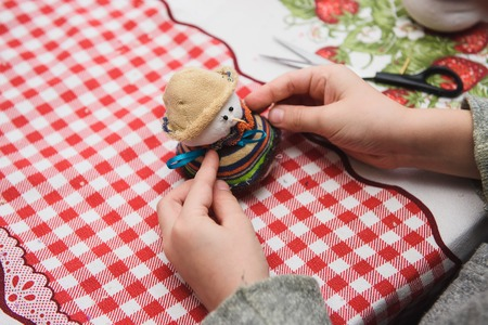 Happy kid doing craft. Small child holding a felt Christmas snowman in hands. Workplace in kindergarten, school or home. Kids Christmas crafts idea. Children winter creativity Standard-Bild