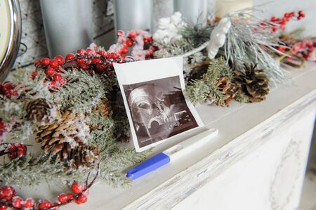 prueba de embarazo: ultrasound picture and a pregnancy test with Christmas decor. close-up.