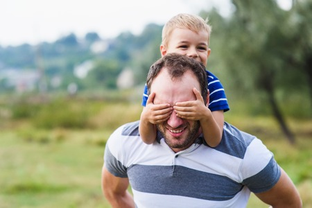 Boy closes hands eyes father. Happy little boy enjoying with riding on fathers back. Happy family portrait. Laughing dad with little boy enjoying nature together.