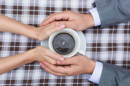 a meeting with a view to marriage: lovers holding together a Cup of coffee.