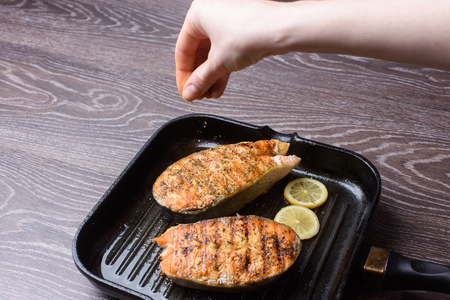 adds: Grilled salmon Steak on grill pan on wooden background. Female adds salt or spices