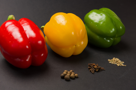 Three bulgarian peppers of different colors lie in a row on black background. Peppers with various spices.