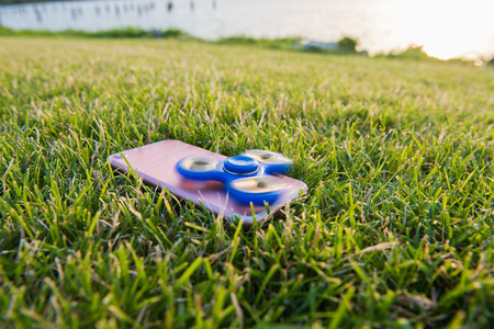 Blue Tri Fidget Hand Spinner on the green grass. Spinner on the phone.
