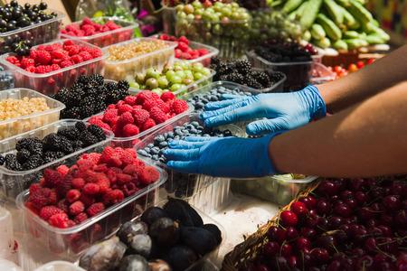 Vendeur préparant des baies fraîches biologiques au marché fermier. Rangées de savoureuses baies fraîches. Banque d'images - 82156685
