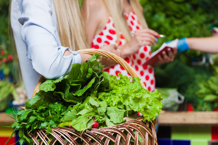 seller: The seller and two blonde women at a vegetable market. Girlfriends buy vegetables on the market. Stock Photo