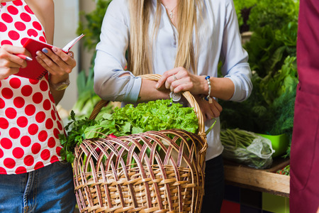 The seller and two girls with a basket of vegetables. Girlfriends buy vegetables on the market. Stock Photo