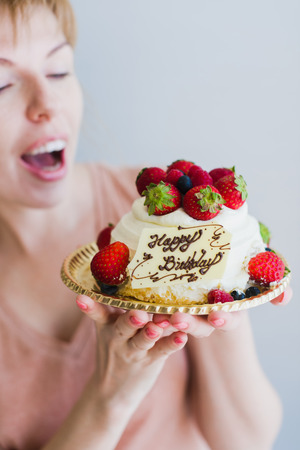 Girl with a birthday cake. Happy lovely young woman holding birthday cake. Gray background Stock Photo