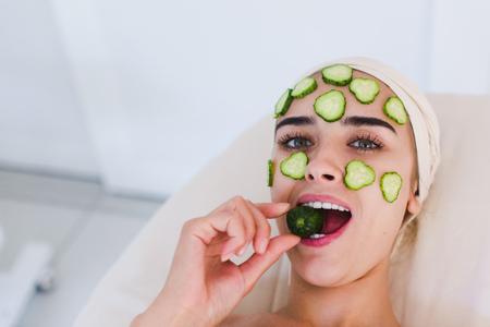 Beautiful young woman receibing facial mask of cucumber in beauty salon