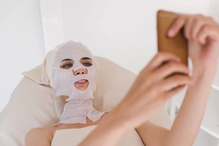 rejuvenate: Woman with facial mask making selfie