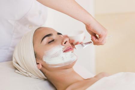 Vrouw met gezicht klei masker.