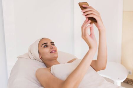 rejuvenate: A girl makes selfie on her phone in a spa Stock Photo