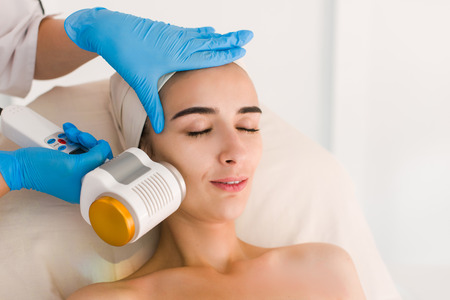Skin care. Young woman receiving facial beauty treatment. Facial therapy. Anti-aging procedures. Woman with closed eyes. Stock Photo