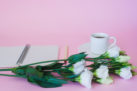 Branch of flowers on a background of a cup of coffee, notepad and pen. Focus on flowers.