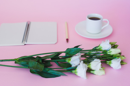 Front view of blank notebook, pen, branch of flowers and cup of coffee over pink background. Focus on flowers. Stock Photo