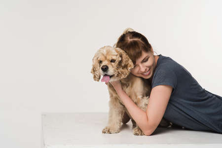 Young woman hugging her American cocker spaniel in white Stock Photo