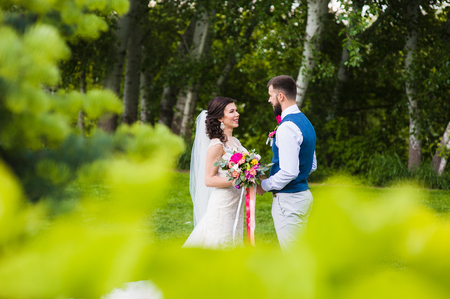 Just marriend young couple in love smiling at nature green background