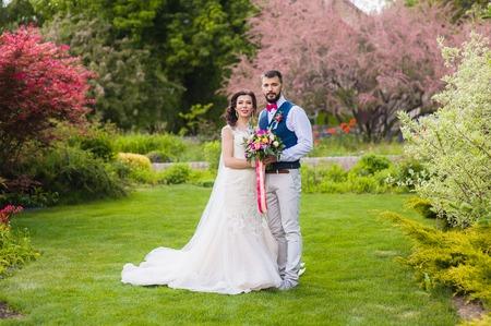 Bride and groom posing in beautiful garden